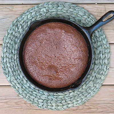 An overhead photo of a cast iron skillet brownie on a green placemat.