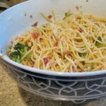 A close up photo of spaghetti with pancetta and broccoli in a bowl.