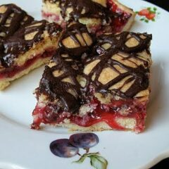 A close up photo of cherry pie squares on a white plate.