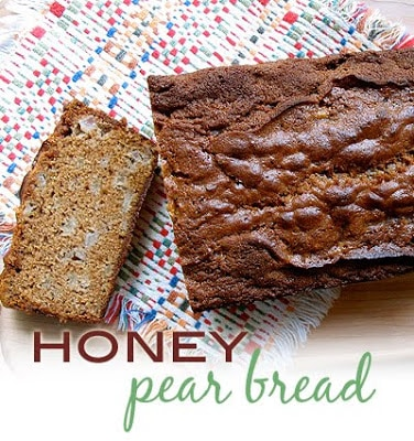 An overhead photo of a loaf of honey pear bread with a slice on the side.