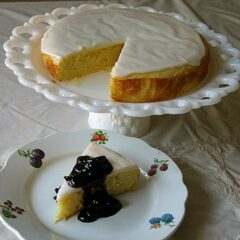 A photo of a lemon cornmeal cake missing a slice on a white cake stand next to a slice of cake on a white plate topped with blueberry sauce.