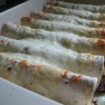A close up photo of shredded beef and Chile enchiladas.