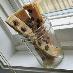 A mason jar holding three cookie sticks.