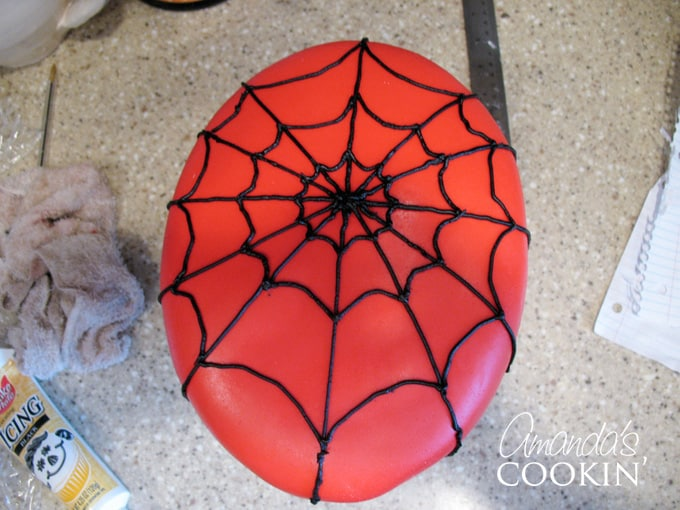 After trimming the fondant (I used the top of my turntable spice rack to place the cake on) to fit snugly around the cake, I then piped on the spider webs.