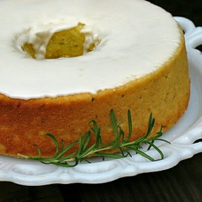 A close up photo of a lemon rosemary olive oil cake resting on a decorative white plate with a rosemary sprig on the side.