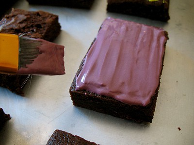 A photo of icing being spread onto a brownie with a paintbrush.