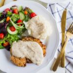 chicken fried steak with white gravy and salad on a plate