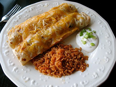 Shredded chicken and Chile enchiladas on a white plate with Spanish rice and sour cream on the side.
