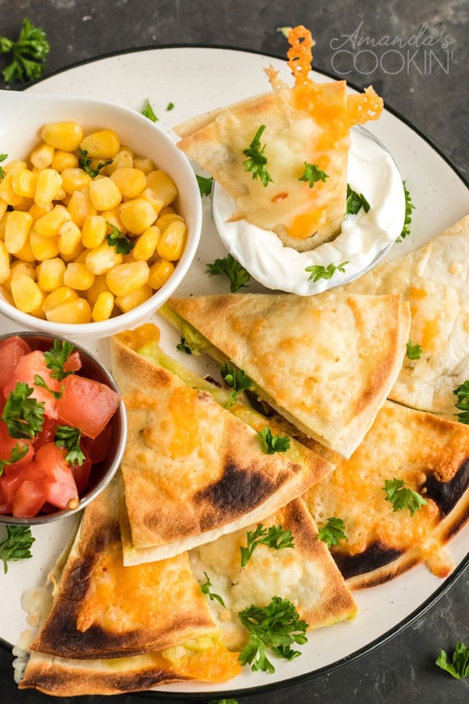 quesados mexican appetizer slices on plate with condiments