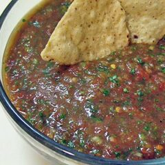 A close up photo of a bowl of homemade salsa with two tortilla chips resting on the side.