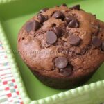 A close up photo of a chocolate chocolate chip muffin in a green dish.