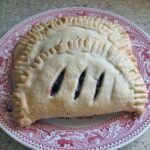 A close up photo of two cherry hand pies resting on a red and white plate.