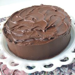A Nigella's old fashioned chocolate cake resting on a white cake stand.