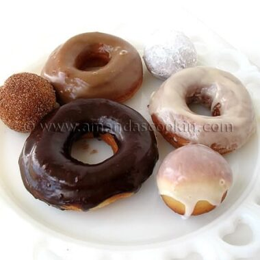 A photo of a plate of an assortment of homemade doughnuts.