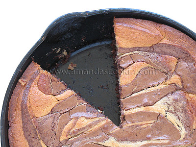 An overhead photo of a peanut butter marbled brownie skillet pie with a slice removed.