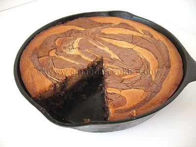 A close up photo of a peanut butter marbled brownie skillet pie with a slice removed.