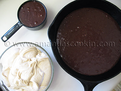 An overhead photo of a skillet filled with brownie batter with a cup of batter to the side and a bowl of the peanut butter mixture in another bowl.