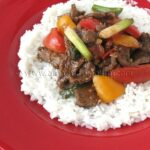 A photo of beef stir fry with tomatoes and peppers over rice.