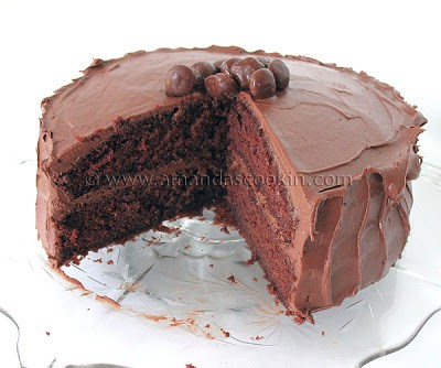 A close up photo of a nigella's chocolate fudge cake with a big slice removed.