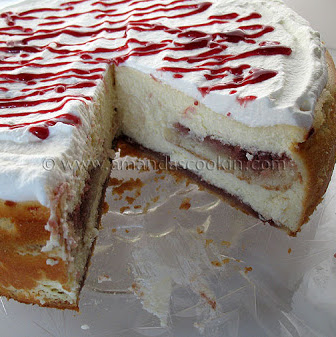 A close up photo of an English trifle cheesecake with a slice removed.