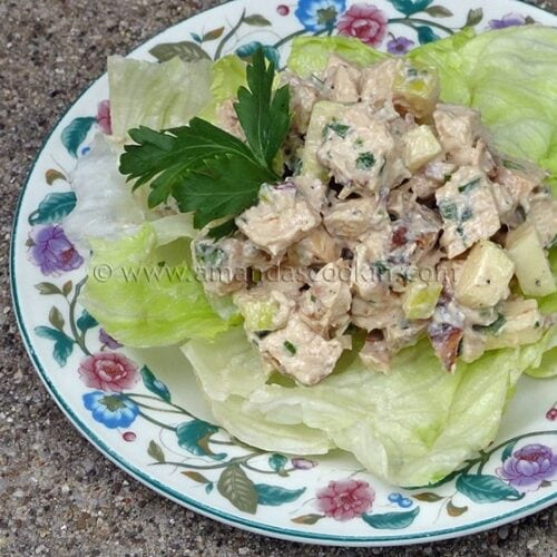A photo of chicken salad on a piece of lettuce.
