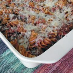 A close up photo of baked rotini with Italian sausage in a baking dish.