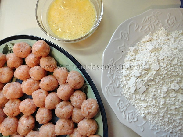 A photo of a plate of raw chicken balls, a bowl of whisked eggs and a plate of flour and salt.