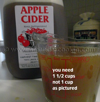 A close up picture of a bottle of apple cider and a cup of apple cider in a measuring cup.