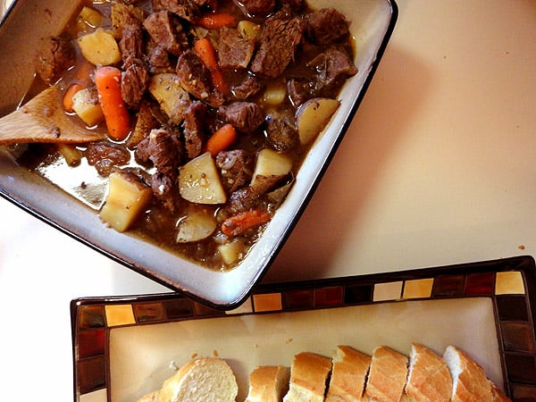 An overhead photo of beef stew with parsley, sage, rosemary and thyme in a square bowl.