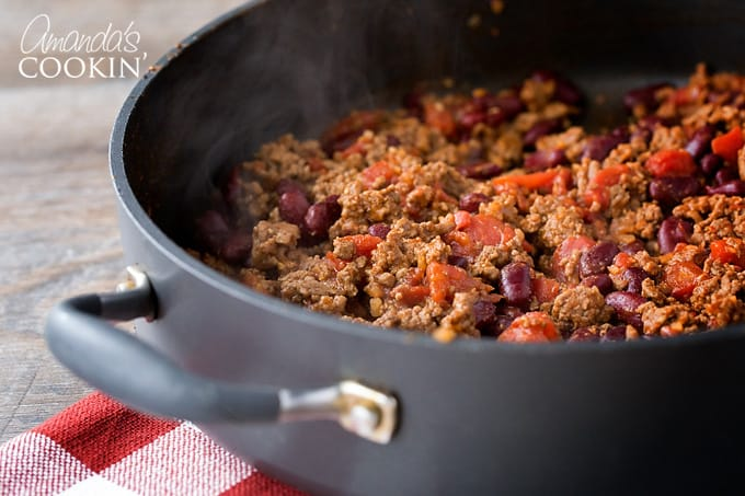 Brown ground beef in a skillet. Drain off fat from ground beef and return beef to pan. Add seasoning mixture, water, beans and tomatoes and stir to combine.