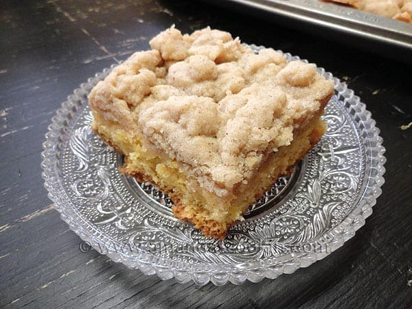 A close up photo of a piece of crumb cake on a clear plate.