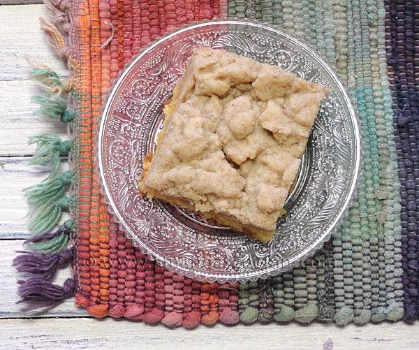 An overhead photo of a piece of crumb cake on a clear plate.