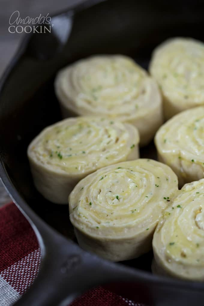 Next you'll slice the rolled dough into discs, just like you do with cinnamon rolls. Place them in a baking pan, or in two cast irons skillets. I used one skillet and one stoneware pan of the same size. You'll brush them with melted garlic butter and sprinkle them with parsley-cheese mixture.