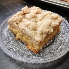 A close up photo of a square of crumb cake on a clear plate.