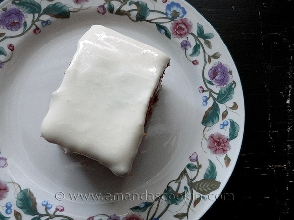 An overhead photo of a square of low fat carrot cake on a decorative plate.