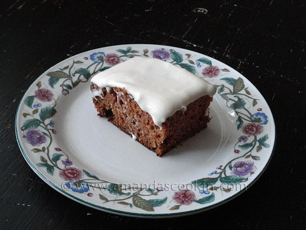 A photo of a square of low fat carrot cake on a decorative plate.