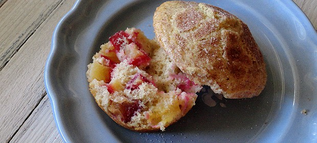 A close up photo of a sugar crusted plum muffin cut in half.
