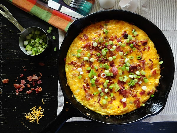 An overhead photo of a cheesy bacon potato frittata in a cast iron pan.