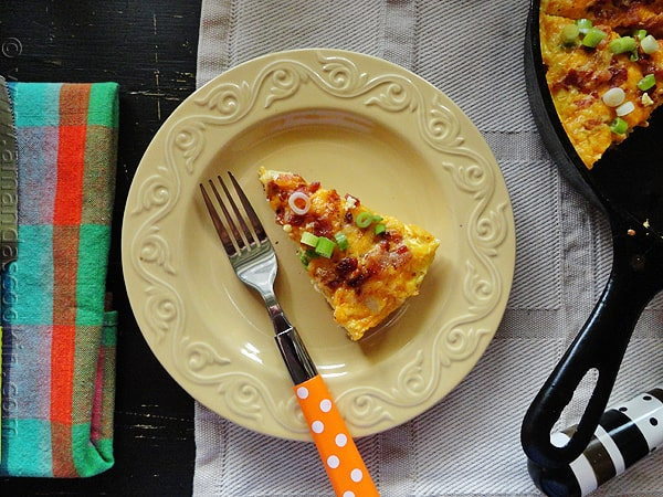 An overhead photo of a slice of cheesy bacon potato frittata on a yellow plate with a fork.