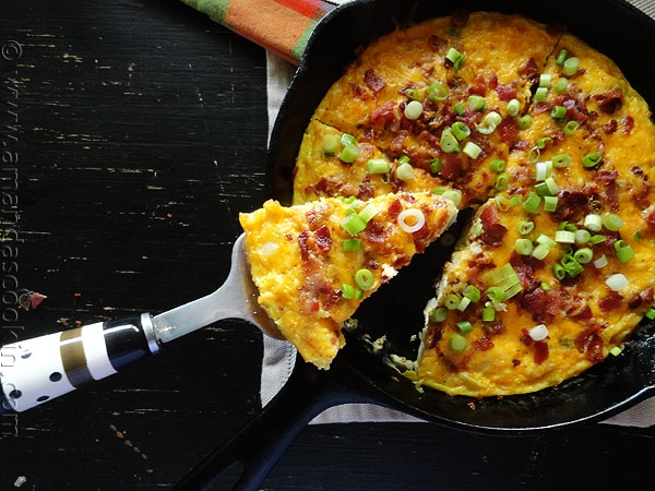 An overhead photo of a slice of cheesy bacon potato frittata being lifted out of the whole pan.