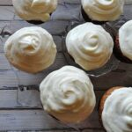 An overhead photo of banana cupcakes with vanilla cream cheese frosting.