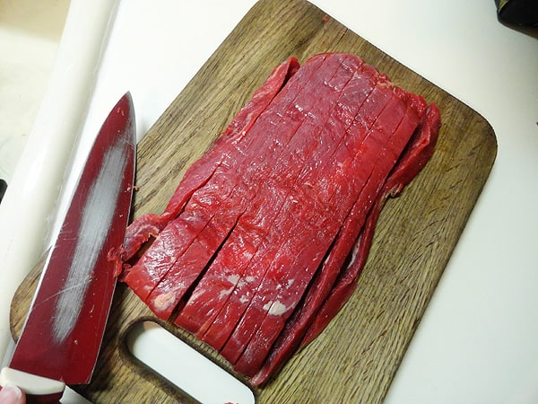 An overhead photo of sliced flank steak on a wooden cutting board.