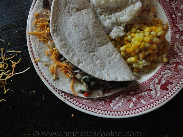 An overhead photo of a steak soft taco resting on a plate with corn and rice to the side.