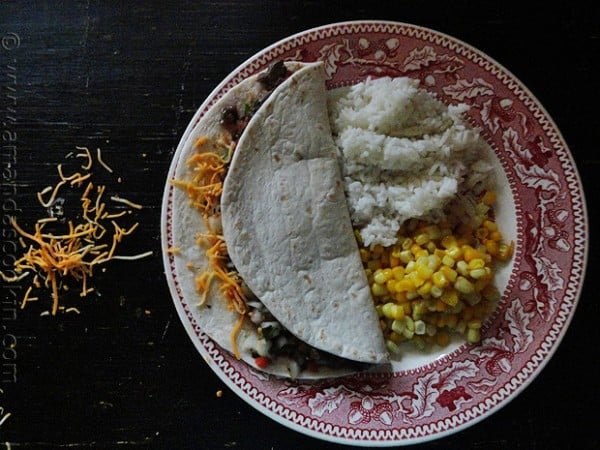 An overhead photo of a steak soft taco on a plate with corn and rice on the side.