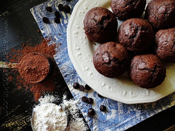 An overhead photo of Starbuck\'s hot cocoa chocolate chip muffins on a white plate with cocoa and flour to the side.
