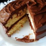 A photo of a classic yellow cake covered in chocolate frosting with a slice removed.