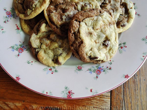A close up photo of a plate of half and half chocolate chip cookies.
