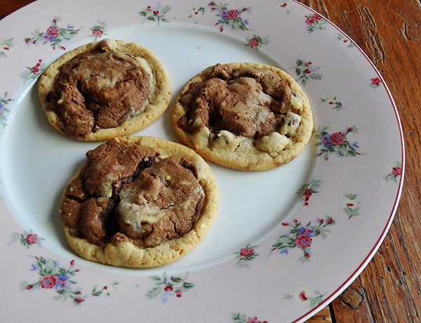 A photo of three half and half chocolate chip cookies resting on a plate.