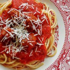 AN overhead photo of a plate of spaghetti and meatballs in marinara sauce.