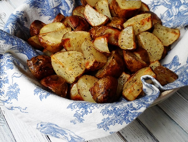 A close up photo of cut up roasted potatoes.